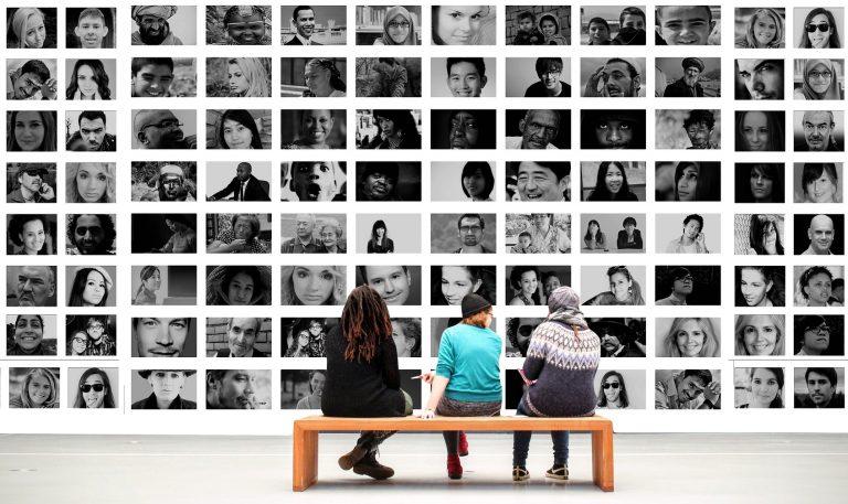 Menschen vor einer Ausstellung mit vielen Gesichtern.