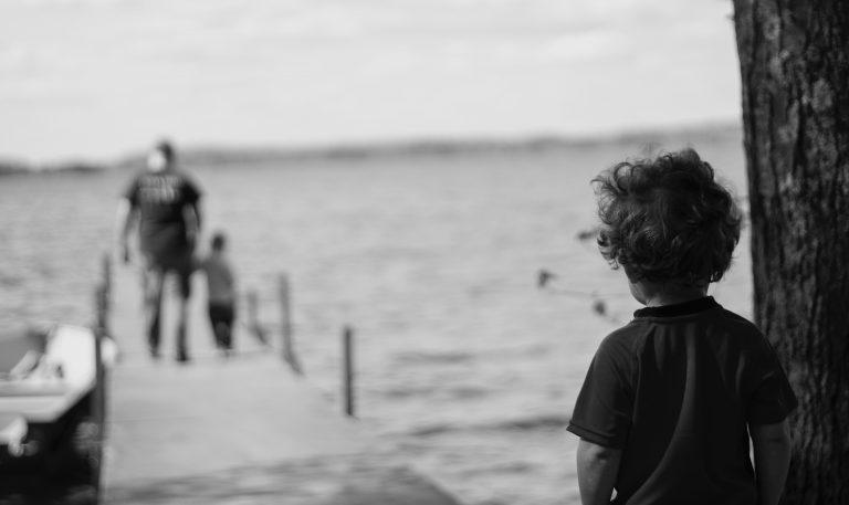 Junge am Steg schaut Erwachsenen und Kind nach