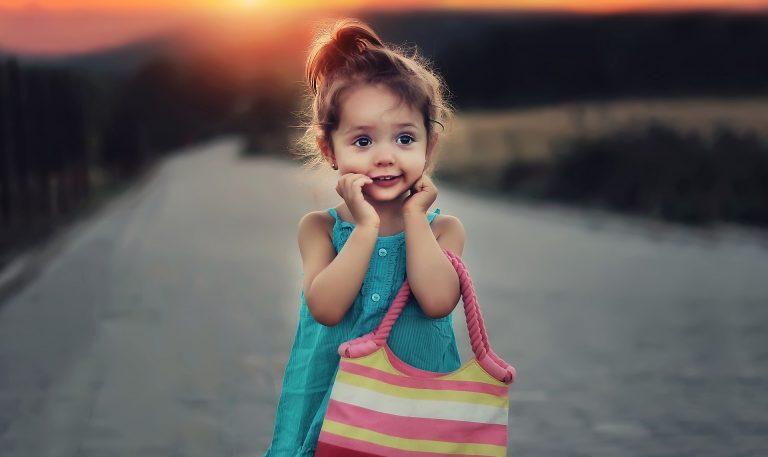 Kind auf einer Straße mit Tasche in der Hand